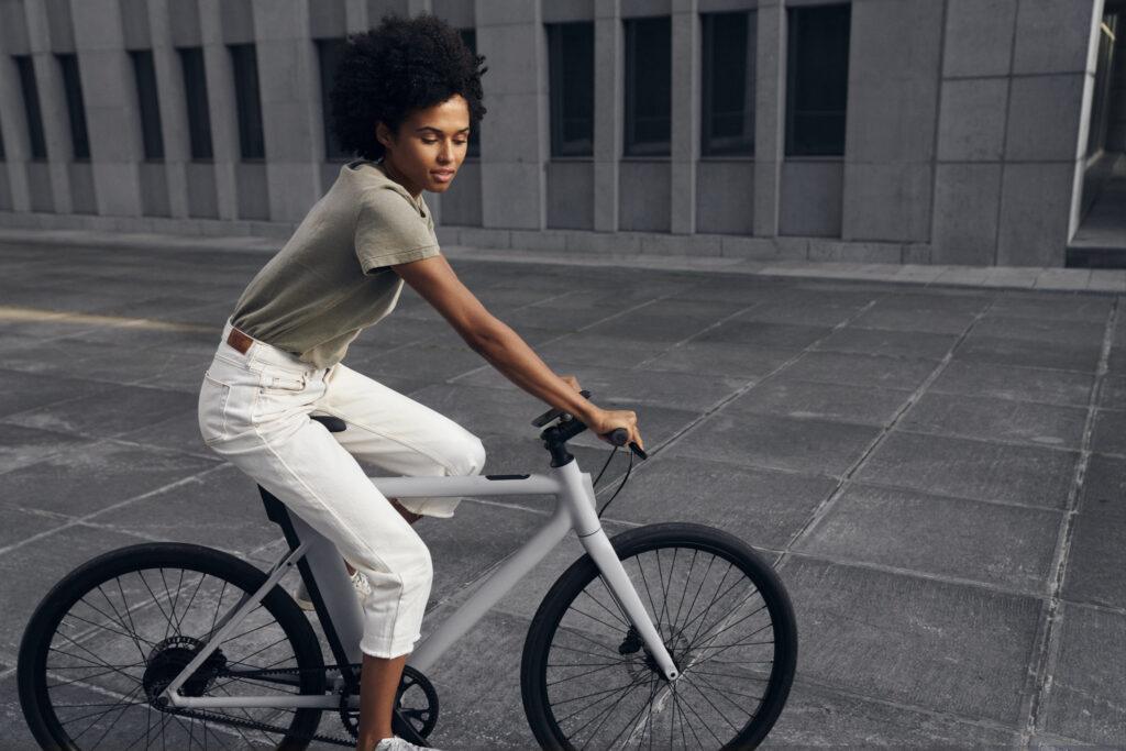 Vrouw op grijze Cowboy fiets met zwarte banden